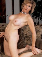 Busty mature lady strips off