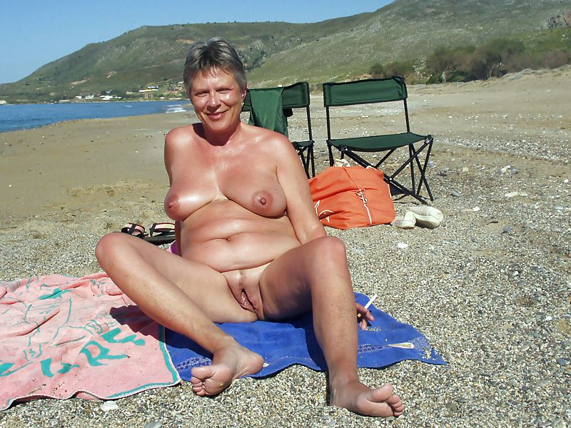 Nude mature woman sunbathing on beach