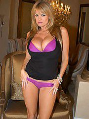 Kelly in a black top and purple lingerie plays with her..