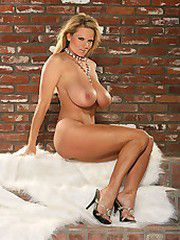 Kelly in a white vest lays down on white fur and poses for..