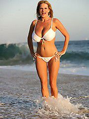 Kelly strolls on the beach in a white..