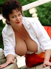 Beautiful mature lady with big breasts posing nude in park