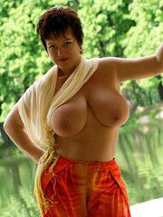 Beautiful mature lady posing naked and showing big breasts..