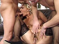 Blonde granny in black stockings plays with two cocks and..