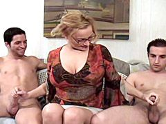 Big tits blonde mature whore jerking and sucking two cocks..